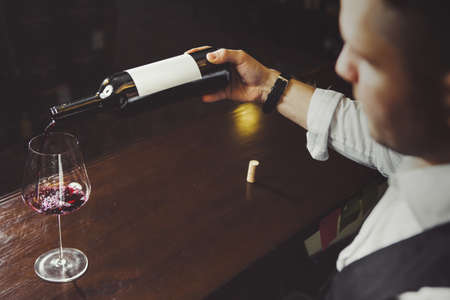 Male sommelier pouring red wine into long-stemmed wineglasses. Banque d'images