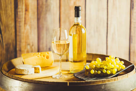 White wine in glass, bottle with grape and cheese on barrel front wood wall background.