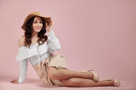Glamorous smiling girl dressing in a stylish hat, white shirt and light brown skirt sits on the floor over pink isolated background. Banque d'images