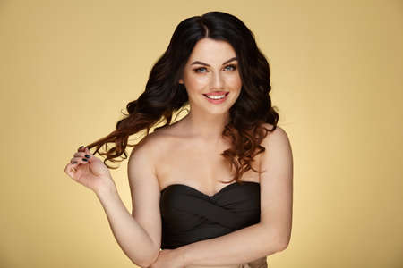 Cute smiling brunette woman with a luxurious and lush hair on a yellow background.