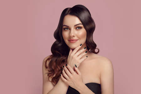 Brunette caucasian woman with a beautiful nude makeup and wavy hair, having a black manicure putting her hands to the face posing over pink isolated background.