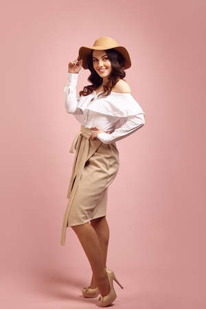 Stylish attractive young brunette woman wearing in beige hat, white shirt and light brown skirt stands over pink isolated background, full length portrait