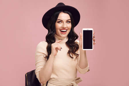 Joyful adult girl points to the blank screen of her phone and smiles in surprise while standing over pink isolated Stock Photo