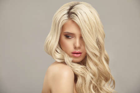 Pretty young blonde woman with nude makeup has a curly long bright hair, close up portrait on beige isolated Stock Photo