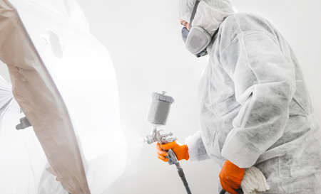 Male worker with mask and protective clothes painting car using spray compressor.
