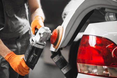Car detailing series: polishing white vehicle in auto repair shop.