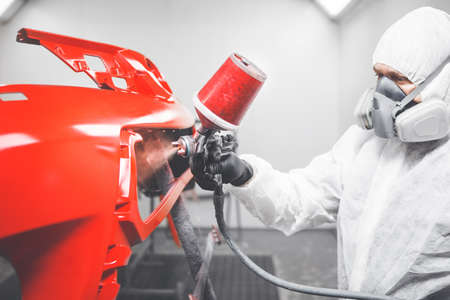 Professional male car painter is painting in garage by airbrush. Man works with spray gun. Stock Photo