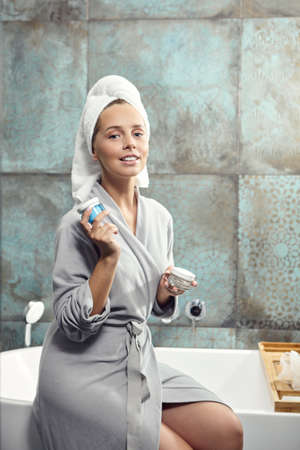 Attractive girl with face cream sitting in bathrobe on the bath. Stock Photo