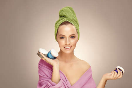 Pretty young woman with natural and healthy skin tone holds multiple creams for face on beige isolated. Stock Photo