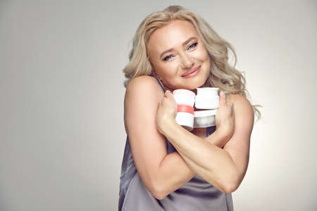 Adult fifty years old woman with clean skin cuddles with love to chest few various jars of moisturizer on a gray isolated background.