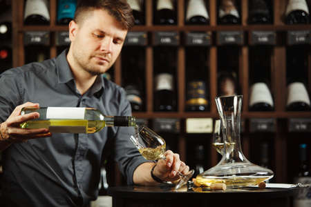 Sommelier pouring white wine from bottle in glass