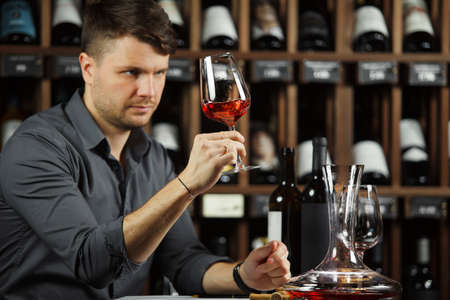 Sommelier looking at red wine glass with beverage Stock Photo