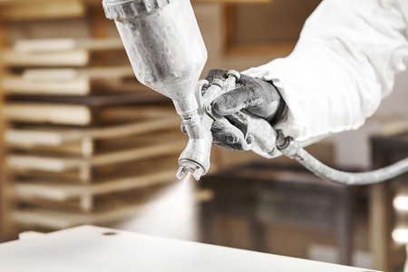 Close-up image of man spraying with gun to the wood.