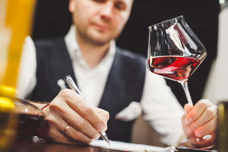 Man fills in paper form holding delicious red wine at table
