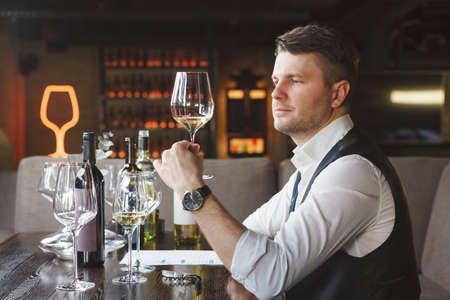 Sommelier looks at white wineglass at table in restaurant