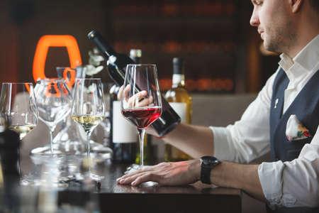 Steward holds wine bottle alcohol beverages in restaurant Stock Photo