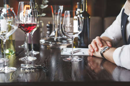 A wine waiter with a tablet near the glasses in the restaurant is waiting for the tasting to begin Stock Photo