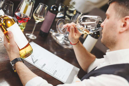 Wine steward with form smells white drink sitting at table
