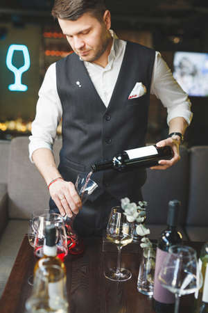 Expert pours delicious red wine into decanter at table Stock Photo