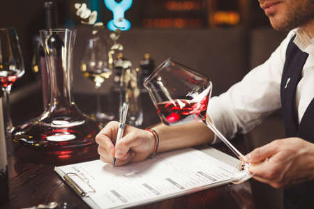 Expert writes holding glass of expensive red wine at table