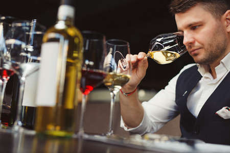 Sommelier smells white wine poured into glass at table