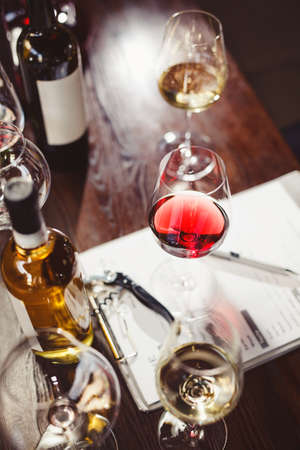 Wineglasses and wine bottles around clipboard on table