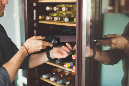Man chooses bottle of delicious wine near cooler in store