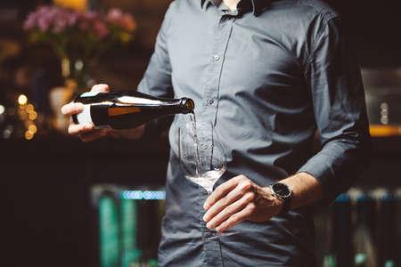 Man pours white wine into wineglass in semi-dark restaurant
