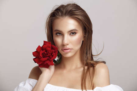 Pretty woman holds red rose flower by chin looking at camera Stock Photo