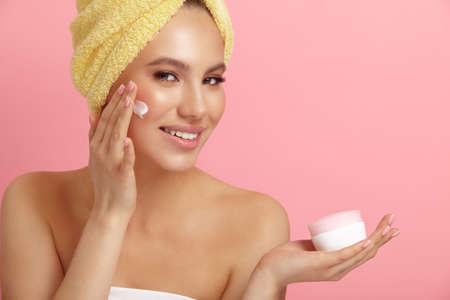 Smiling young woman with clean skin applies cream on face showing jar on pink