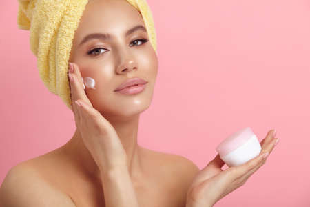 Seductive female model applies cream on cheek at pink wall