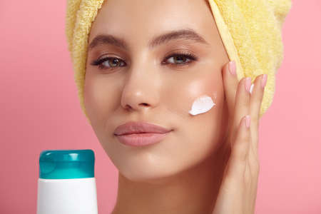 Young woman applies lotion on cheek showing blank tube Stock Photo