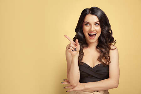 Studio shot pleased caucasian ethnicity woman with a luxurious brunette hair points away with finger, shows blank space for your text, isolated on yellow background.