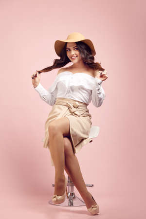 Charming young caucasian woman with a cute smile wearing a beautiful hat, wide white shirt and stylish light brown skirt, holding her hair with both hands, sitting on high chair over pink isolated.