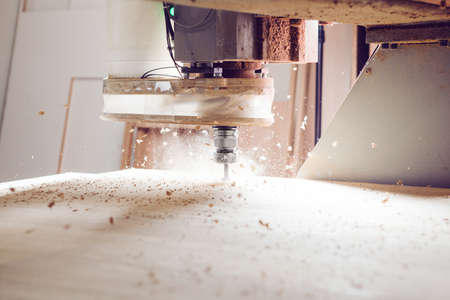 Cnc machine at carpentry workshop. Cutting wood with various router bits. Stock Photo