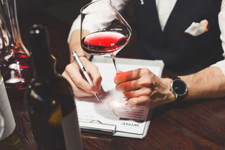 Sommelier writes on clipboard describing red wine at table