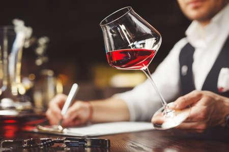 Sommelier fills form describing taste of red wine at table. Degustation of alcoholic beverages. Stock Photo