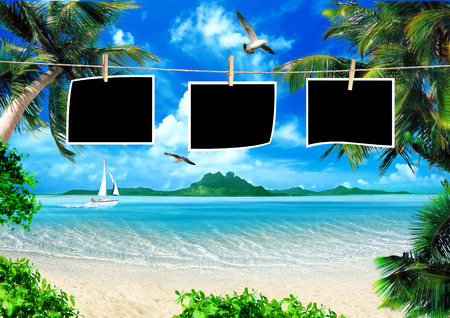 polaroid frame: Tropical coast, beach with photo frames on clothesline and hang palm trees. View of the Sea, the island green and the sky with large clouds. Stock Photo