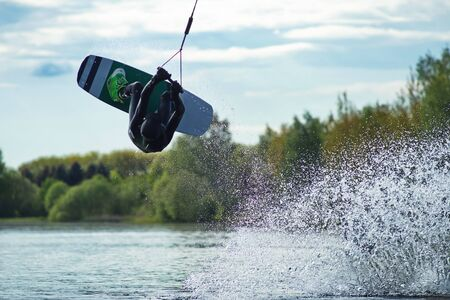 Wakeboarder making tricks. Low angle shot of man wakeboarding on a lake.