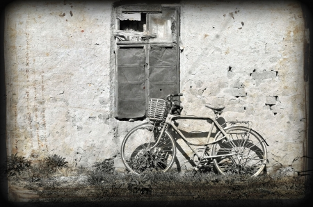 old bicycle leaning against a ruined wall. Photo in old image style.  photo