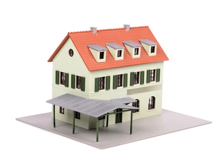 A model of house with dark roof on a white background