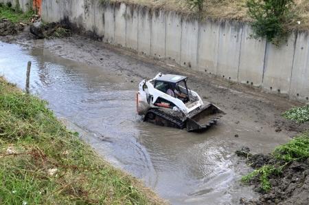 small excavator Bobcat along river Stock Photo
