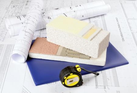 stucco facade: Pezzo di gesso, colla, polistirolo, rete di protezione, termica su sfondo disegni architettonici