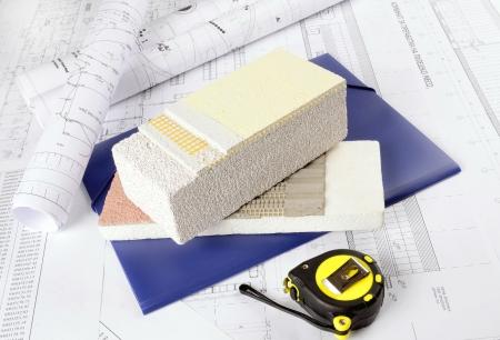 materiales de construccion: Pedazo de yeso, pegamento, poliestireno protecci?n t?rmica neta, en el fondo dibujos arquitect?nicos