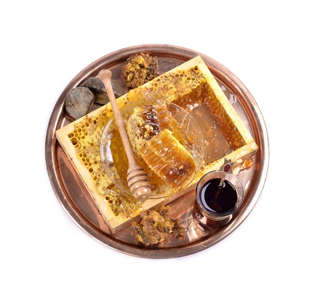 fresh honeycombs and wooden stick ,cup of Turkish tea,propolis, isolated on white background  photo