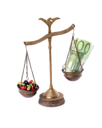 health care funding: Conceptual photo: high cost of medicine.Old scale isolated white