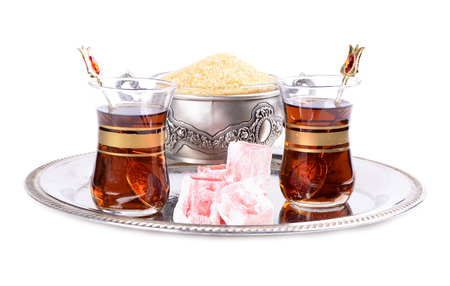 Turkish tea in a glass cup on a tray,Turkish delight and brown sugar