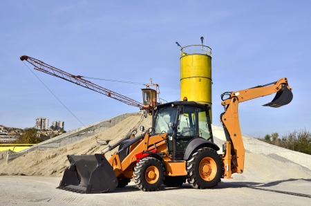 Wheel loader Excavator unloading sand of construction site concrete plant. photo