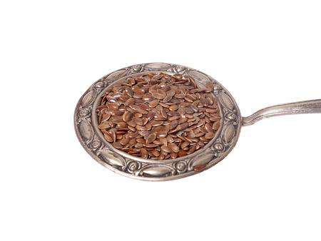 Linseed  on a metal spoon isolated on White Background photo