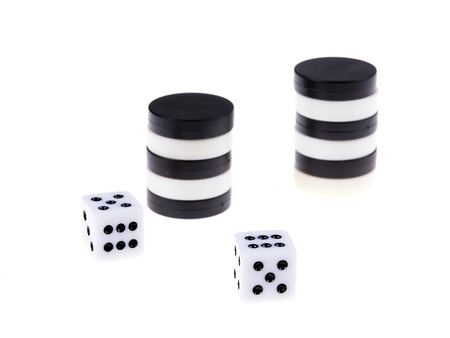 gambling counter: Stacked backgammon black and white pieces and dice isolated on white background Stock Photo